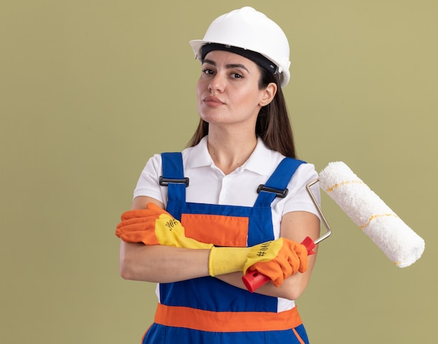 ローラー ブラシを保持し、オリーブ グリーンの壁に分離された手を交差する制服と手袋を着た自信のある若いビルダーの女性