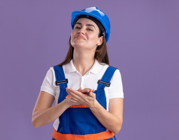 紫の壁に手を繋いでいる制服を着た自信のある若いビルダーの女性
