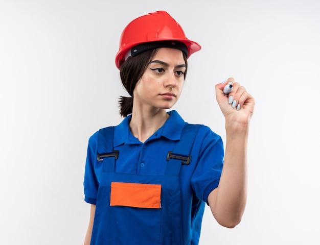 Уверенная молодая женщина-строитель в униформе, держащей маркер