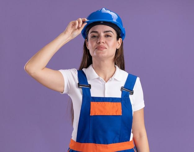 Уверенная молодая женщина-строитель в униформе, держащая защитный шлем, изолированную на фиолетовой стене