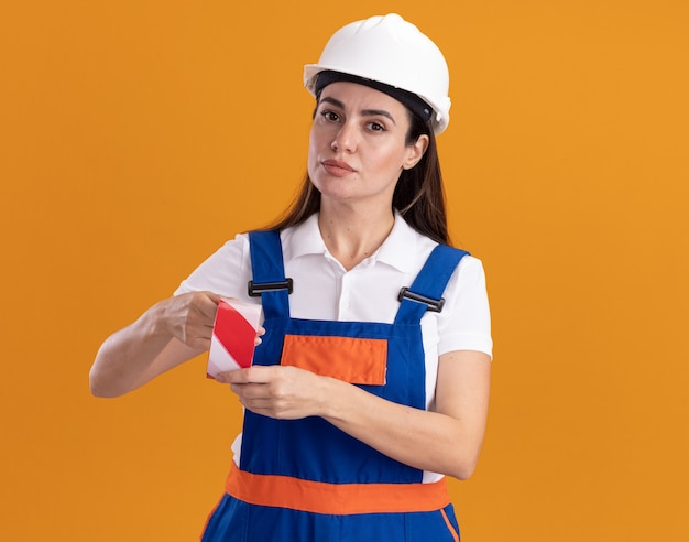 Confident young builder woman in uniform holding duct tape isolated on orange wall