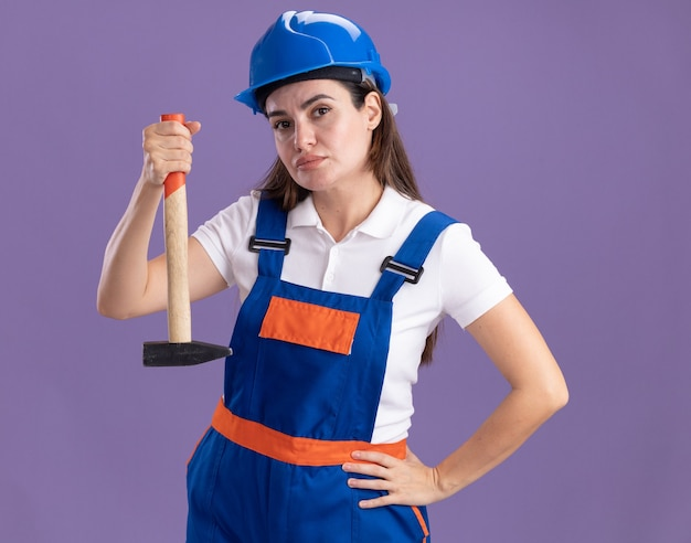 Confident young builder woman in uniform holding hammer putting hand on hip isolated on purple wall