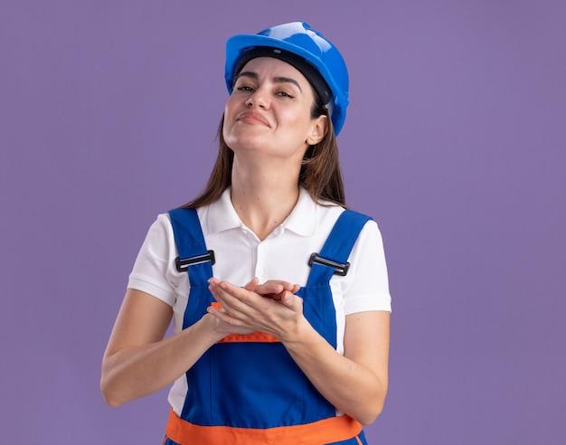 Fiduciosa giovane donna costruttore in uniforme che si tiene per mano insieme isolata sul muro viola purple