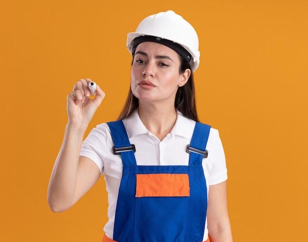 Fiducioso giovane donna costruttore in uniforme che porge marcatore alla telecamera isolata sul muro arancione