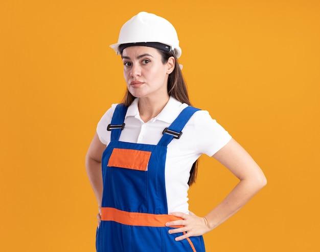 Giovane donna sicura del costruttore in uniforme che mette le mani sull'anca isolata sulla parete arancione