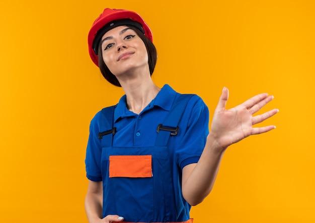 Giovane donna sicura del costruttore in uniforme che mostra gesto di arresto isolato sulla parete gialla