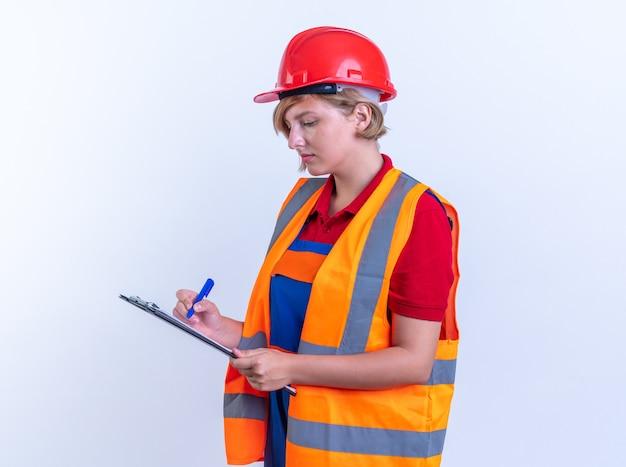 Fiduciosa giovane donna costruttore in uniforme che scrive qualcosa negli appunti isolati su muro bianco
