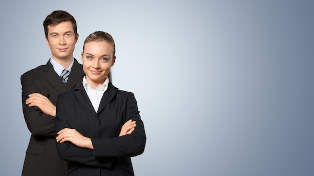 Уверенный молодой бизнес пара со скрещенными руками на фоне