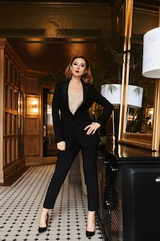 Confident young business lady in black suit posing in vintage interior