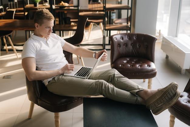 자신감 있는 젊은 사업가가 햇볕이 잘 드는 사무실에서 노트북에 타이핑을 하고 있다