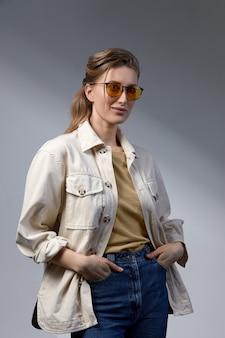 自信を持って若いビジネスウーマン35-45歳、スタイリッシュなフォーマルな服とメガネ、灰色の背景、クローズアップで金髪。ビジネスとキャリアの成功の概念。