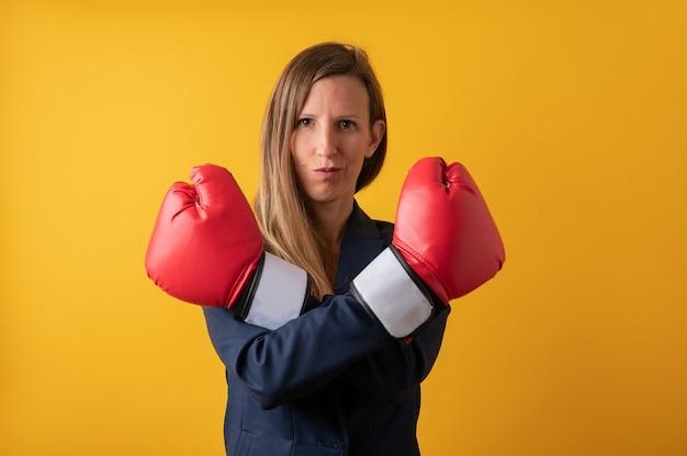 빨간 권투 글러브와 그녀의 손을 넘어 자신감 젊은 비즈니스 여자. 노란색 배경 위에.