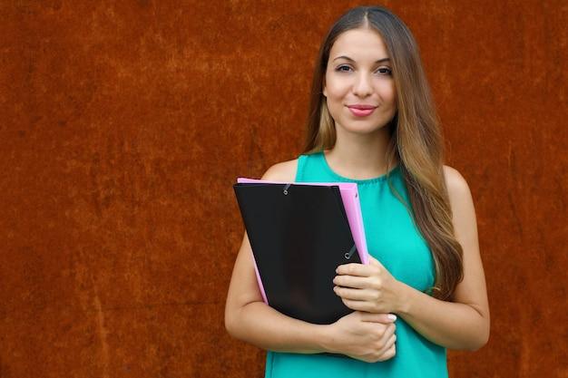 フォルダーを保持している自信を持って若いビジネス女性はコピースペースと錆の背景にカメラを見てください。
