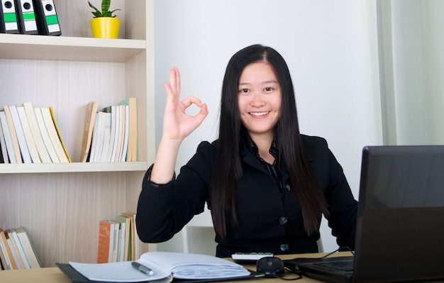 Confident young business woman, showing ok sign , working in the office.
