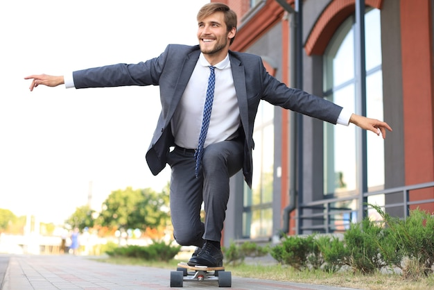 Confident young businessman in business suit on longboard hurrying to his office, on the street in the city.
