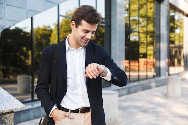 Уверенный молодой бизнесмен, несущий сумку, прогулки на свежем воздухе