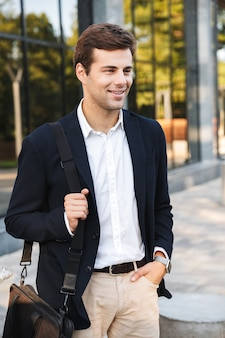자신감이 젊은 사업가 가방을 들고 야외에서 걷기
