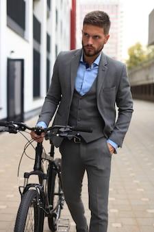 屋外を歩きながら自転車を運ぶ自信のある青年実業家。