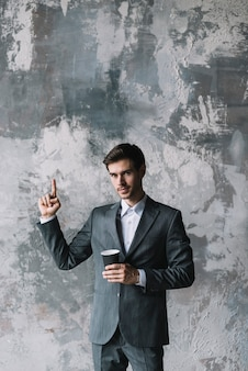 Confident young businessman holding takeaway cup pointing finger upward against concrete wall