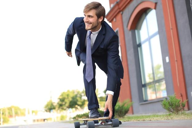 街の路上で、彼のオフィスに急いでロングボードでビジネススーツを着た自信のある青年実業家。