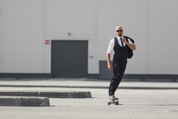 Уверенный молодой бизнесмен в деловом костюме на longboard, спешащий в свой офис