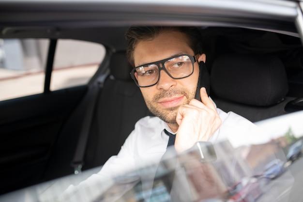 Уверенный молодой бизнесмен в очках сидит в машине, едет на работу и разговаривает с клиентом на смартфоне
