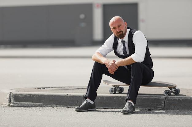 현대적인 건물 근처에 longboard를 사용하여 거리를 걷고 안경에 자신감이 젊은 사업가