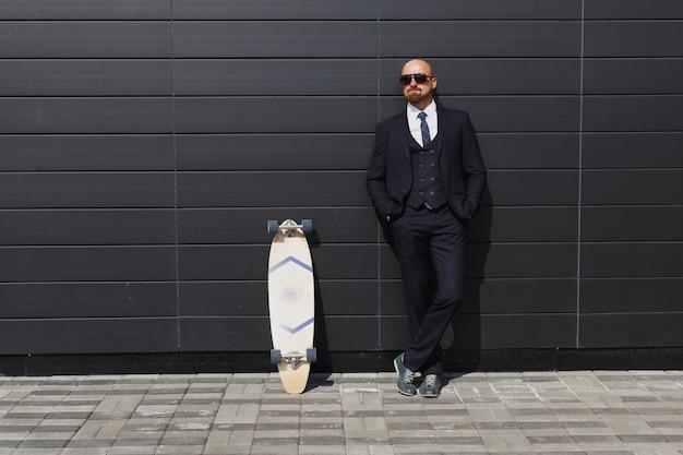 Уверенно молодой бизнесмен в очках, идя по улице, используя longboard.