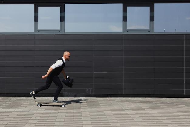 Longboard를 사용 하여 거리를 걷고 안경에 확신 젊은 사업가.