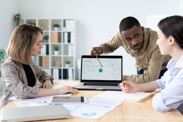 ノートパソコンのディスプレイ上の図を指差しながら同僚の一人を見ているアフリカ民族の自信を持って青年実業家