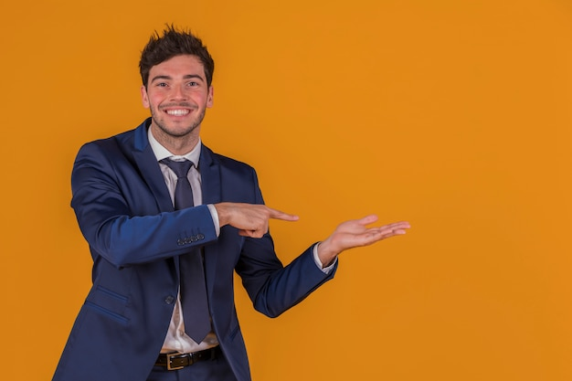 Confident young businessman pointing finger at something against an orange background