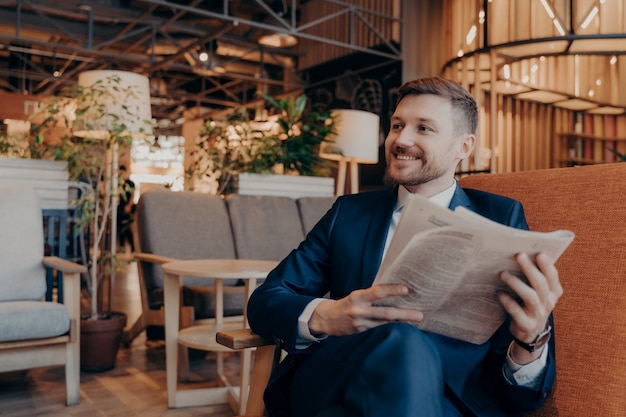 Confident young businessman reading newspaper and latest financial news articles while sitting in armchair in modern cafe shop interior while waiting for work colleague to have morning coffee together