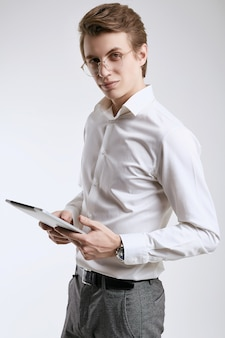 Confident young businessman in shirt working on digital tablet