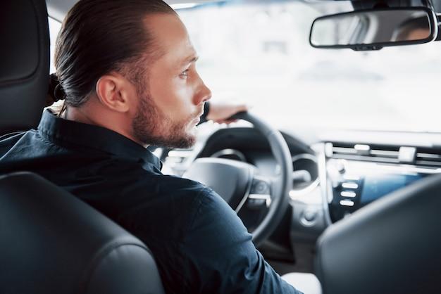 Уверен молодой бизнесмен, сидя за рулем своего нового автомобиля
