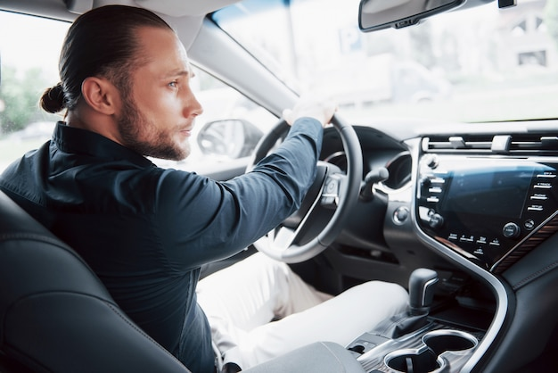 그의 새로운 자동차의 바퀴에 앉아 확신 젊은 사업가