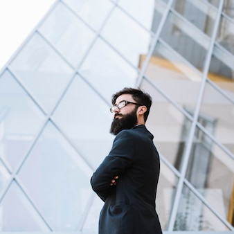 Confident young businessman standing in front of glass building