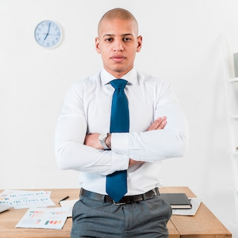 Confident young businessman standing in front of wooden table with his arm crossed