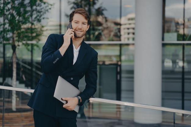Уверенный молодой бизнесмен, стоящий снаружи с портативным компьютером и разговаривающий по мобильному телефону