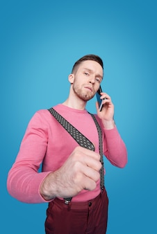 Confident young businessman stretching suspender while standing and communicating on smartphone