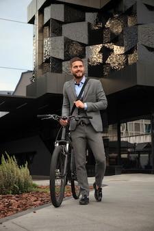 町の通りを自転車で歩く自信のある青年実業家。