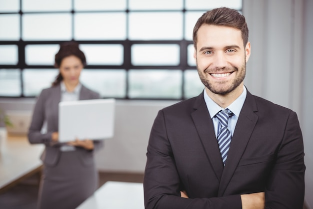 Confident young businessman while colleague in background