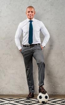 Уверен молодой бизнесмен с руками в кармане и ногой на футбольный мяч против серой бетонной стены