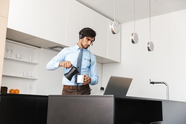 ラップトップコンピューターを使用して、ヘッドフォンセットを介して通信し、キッチンで自宅で働く自信のある青年実業家