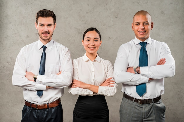 Confident young businessmen and businesswoman with their arms crossed looking to camera