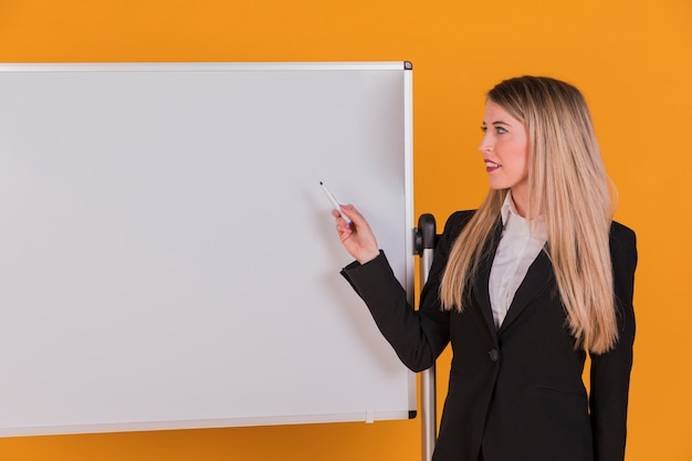 Confident young businesswoman giving presentation on whiteboard against an orange backdrop