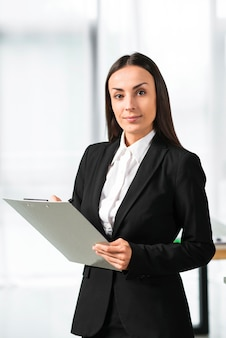 Confident young businesswoman holding clipboard looking at camera