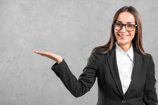 Confident young businesswoman presenting against gray background