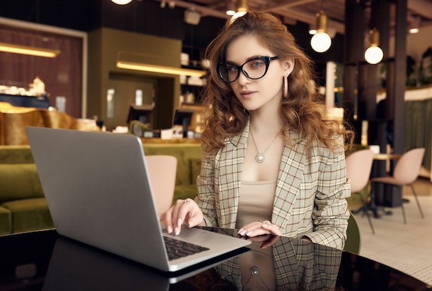 Confident young businesswoman in smart casual wear working on laptop