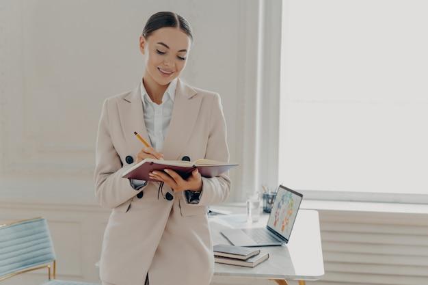 Уверенная молодая деловая женщина, стоящая на рабочем месте в стильном интерьере в современном офисе, улыбается профессиональная женщина-предприниматель в бежевом официальном костюме, отмечая ее график работы карандашом