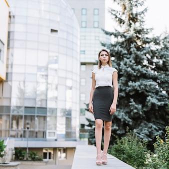 Giovane donna di affari sicura che si leva in piedi davanti all'edificio per uffici